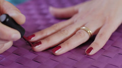 Woman putting on nail polish on finger nails: red, brush, manicure Stock Footage