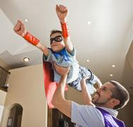 Father holding aloft his son (8-9) dressed up in fancy dress costume Stock Photos