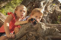 Little boy and little girl (6-7) looking at something in the distance with Stock Photos