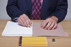 Man writing on paper with tiny pencil - stock photo