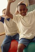 Students playing on exercise balls in classroom Stock Photos