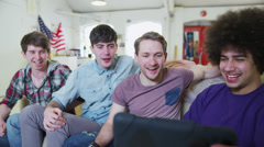 Happy casual group of young male friends relaxing with a tablet computer Stock Footage