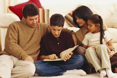 Young boy reading to his family - stock photo