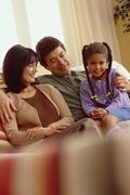 Young girl and her parents relaxing on the couch - stock photo