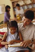 Young girl reading with her father - stock photo