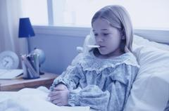 Young girl sick in bed Stock Photos