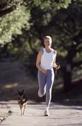 Nainen käynnissä koiraansa Kuvituskuvat