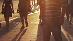 People walking at sunset, long shadows of people on the sidewalk in a city Stock Footage