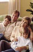 Family relaxing on couch together Stock Photos