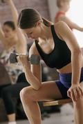 Woman lifting free weight at gym Stock Photos