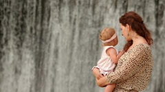 Mother and her little daughter on the background of a waterfall Stock Footage