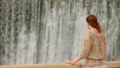 Young woman back to the viewer standing at a waterfall Stock Footage