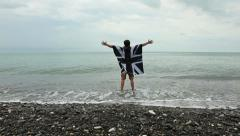 Young man in raincoat with a picture of British flag on seacoast Stock Footage