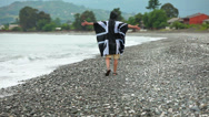 Stock Video Footage of Young man in raincoat with a picture of British flag on seacoast