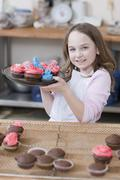 Young girl holding a plate of cupcakes - stock photo