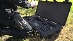 Stock Video Footage of crime & justice, police Tac team member checking weapon, handgun