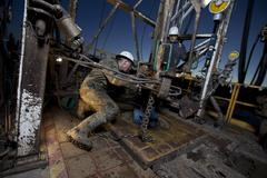 Canada, Alberta, Oil workers using oil drill - stock photo