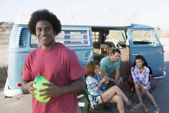 Man in foreground holding rugby ball with friends during their road trip Stock Photos