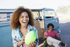 Woman in foreground holding rugby ball with friend during their road trip Stock Photos