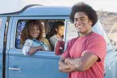 Man in foreground with friends during their road trip Stock Photos