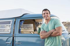Man in front of his mini van during road trip Stock Photos