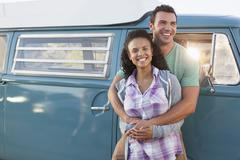 Young couple in front of mini van during road trip Stock Photos