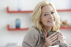 Young woman relaxing at home and holding mug Stock Photos