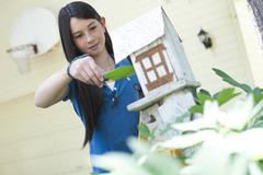 Nuori tyttö laittoi linnun siemenet linnunpönttö Kuvituskuvat