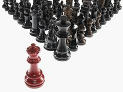 Black chess pieces with opposing queen - stock photo