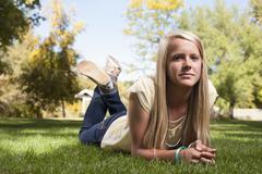 Stock Photo of USA, Utah, outdoor of  blonde girl  (12-13) lying on grass