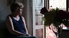 thoughtful and sad old woman near the window: problem, trouble, sadness - stock footage