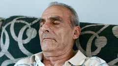 An old man makes an afternoon nap and wakes up Stock Footage