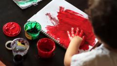 View from behind on child paints a sheet of paper by hand - stock footage
