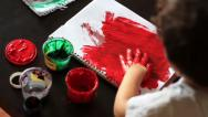 Stock Video Footage of View from behind on child paints a sheet of paper by hand