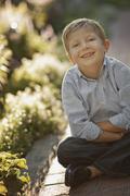 Stock Photo of Portrait of boy (6-7) sitting on garden path