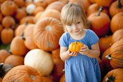 Stock Photo of USA, Utah, Orem, portrait of girl (2-3) holding pumpkin