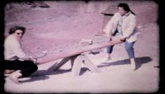 women on teeter totter at western tourist stop, 208 vintage film home movie Stock Footage