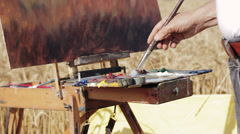 painter mixes with the brush colors in his palette and paints his canvas - stock footage