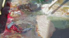 painter mixes with the brush colors in his palette - stock footage