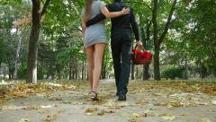 Couple walking with basket for picnic in the autumn park Stock Footage