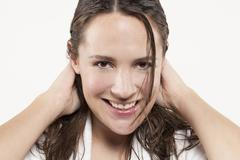 Portrait of woman with long wet hair, studio shot - stock photo