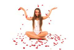 beautiful young woman with rose petals flying - stock photo