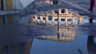 Stock Video Footage of after a storm people walking reflected on a puddle in front of coliseum