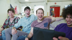 Happy casual group of young male friends relaxing with a tablet computer - stock footage