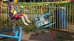 Little girl riding on chained carousel Stock Footage
