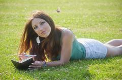 Girl lying on the grass finds inspiration in a butterfly Stock Photos