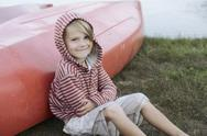 Stock Photo of Portrait of boy (4-5) sitting by canoe