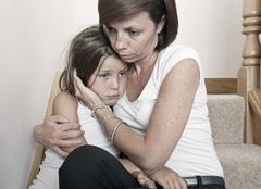 Mother consoling sad daughter (6-7) - stock photo