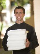 Man from room service delivering towels to hotel guest Stock Photos