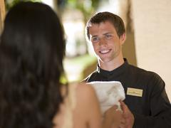 Man from room service delivering towels to hotel guest - stock photo